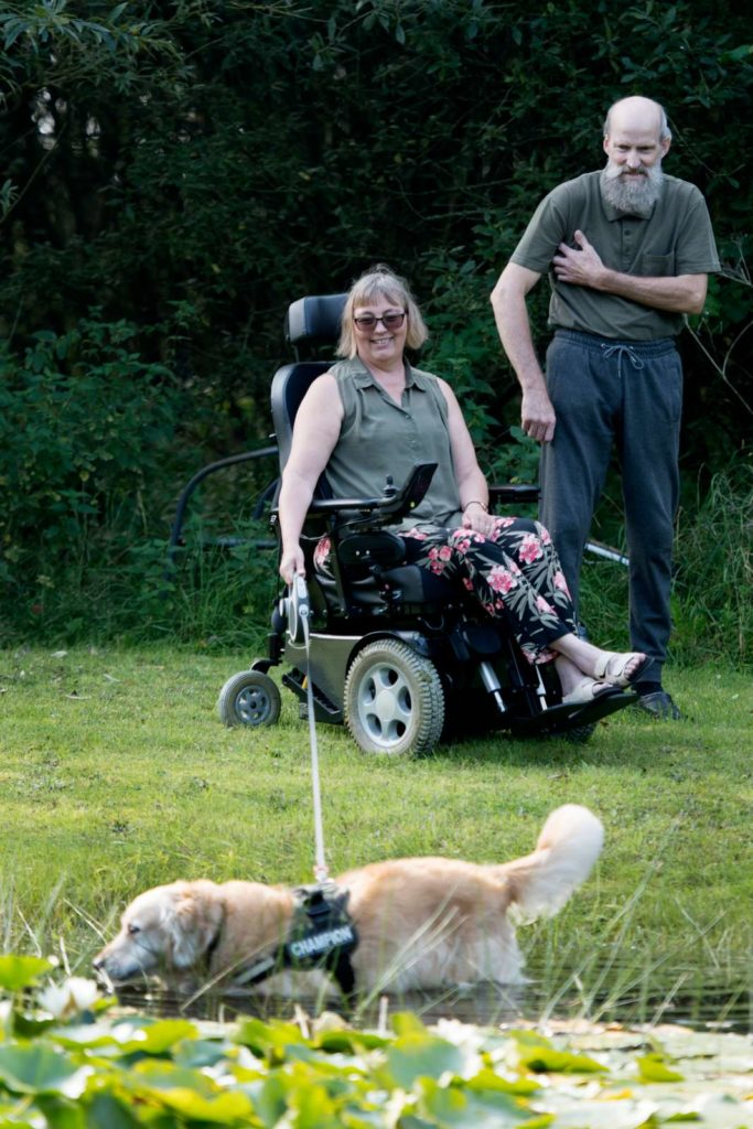 Kvinde i kørestol med hund i snor og en mand gående ved siden af.