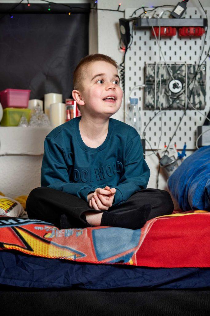 Dreng sidder i sin seng