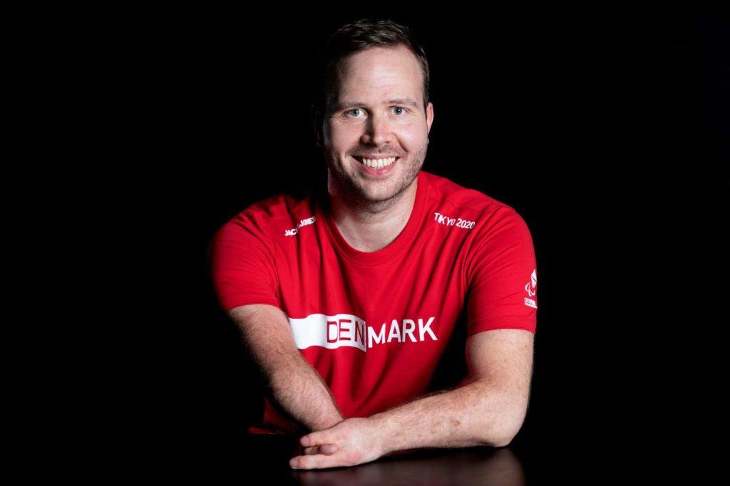 Mand i rød trøje smiler