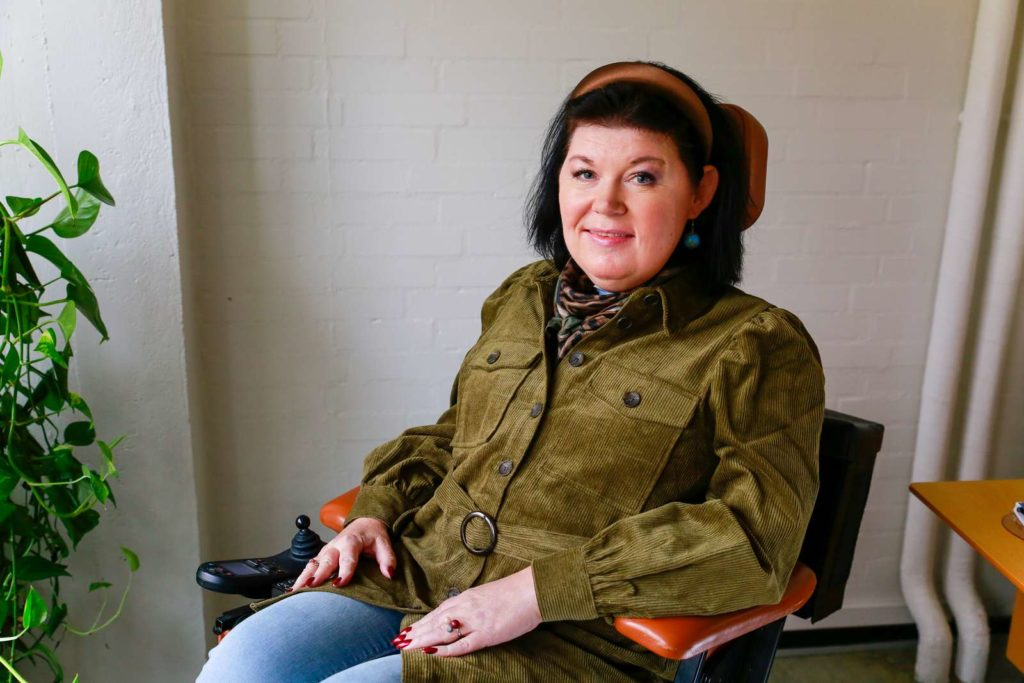 Kvinde i kørestol smiler til kameraet
