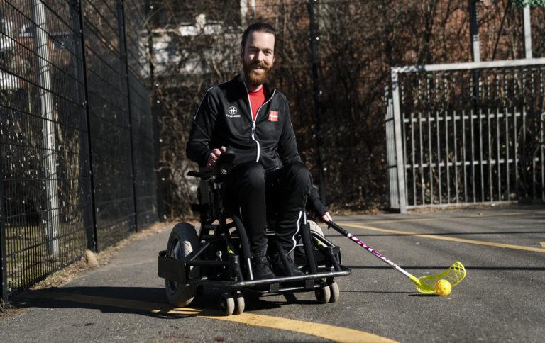 Anders i sin el-kørestol med floorball-stav i hånden