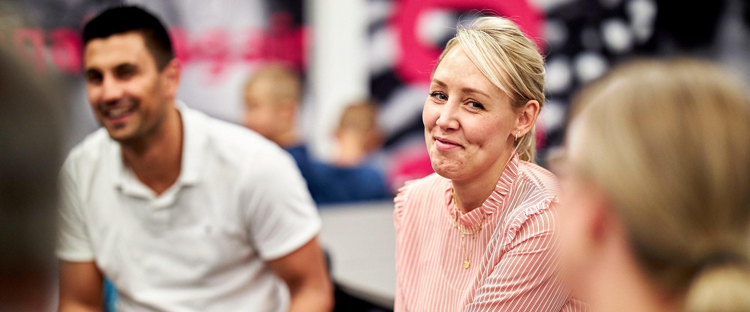 Kvinde smiler siddende i en forældregruppe